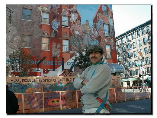 Color picture of community artist Manny Vega.  In the background stand the East 104th street wall mural which he has restored